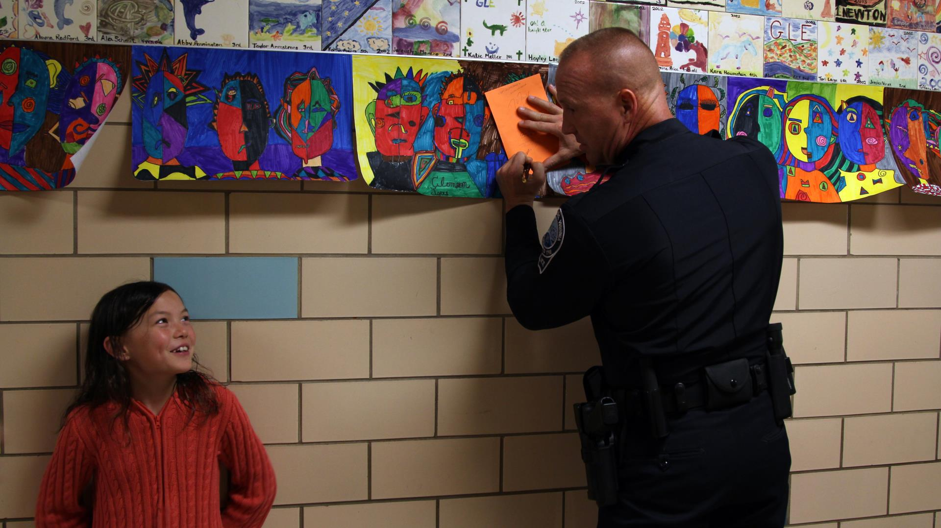 Student at Gilbert Linkous Elementary looking up at Officer Nathan O'Dell