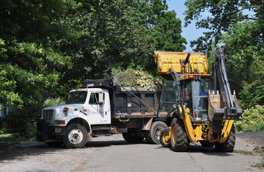 Town of Blacksburg backhoe and dump truck cleaning up after a bad storm
