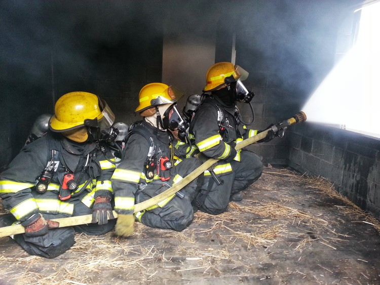 Three Blacksburg Firefighters putting out fire during a training