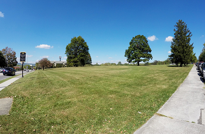 View of the Old Blacksburg Middle School site with grass and sidewalk in view looking toward downtown Blacksburg.