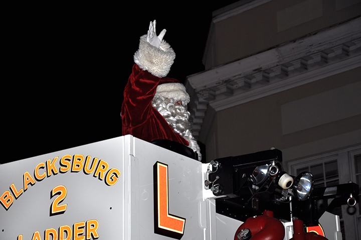 Santa waving while riding in ladder truck