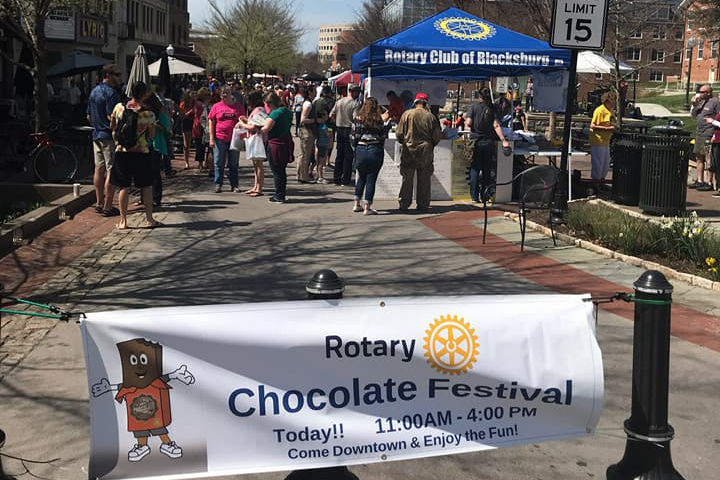 Chocolate Festival banner on bollards on College Avenue with Rotary tent and people in the background