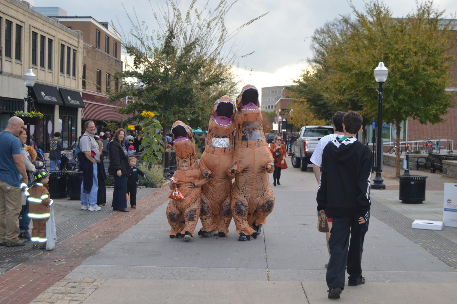 Family in inflatable dinosaur costumes walking down College Avenue on Halloween