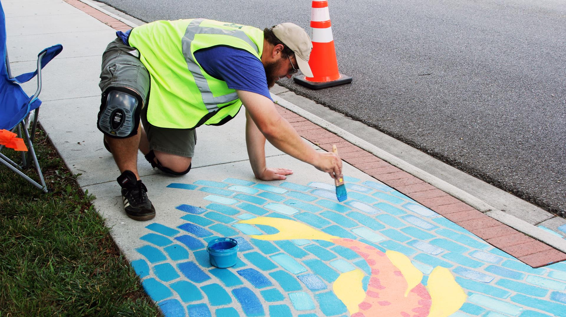 Michael St Germain painting his stormwater arts project on Clay Street